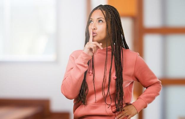 Portret młodej czarnej kobiety w warkoczach trzymającej sekret lub proszącej o ciszę, poważną twarz, posłuszeństwo