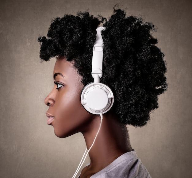 Portret młodej czarnej kobiety z kręconymi włosami słuchającej muzyki z białymi słuchawkami