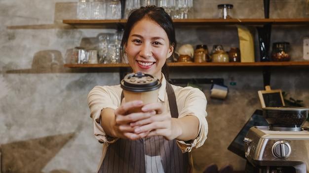 Portret młodej damy azjatyckich barista kelnerka trzymając filiżankę kawy uczucie szczęścia w miejskiej kawiarni.