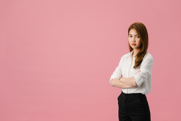 Portret młodej damy azji z pozytywnym wyrazem twarzy, skrzyżowanymi rękoma, szeroko uśmiechniętym, ubrana w swobodny strój i patrząca w kamerę na różowym tle.