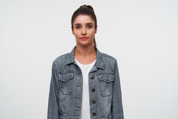 Portret młodej damy brunetka ubrana w biały t-shirt i dżinsowe kurtki, patrzy w kamerę ze spokojnym wyrazem, stoi na białym tle.