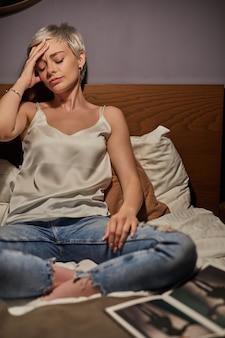 Portret młodej damy cierpiącej na ból głowy, siedzącej samotnie na łóżku w domu, kobiety dotykającej głowy, znudzonej i wyczerpanej, potrzebującej odpoczynku, przygnębionej