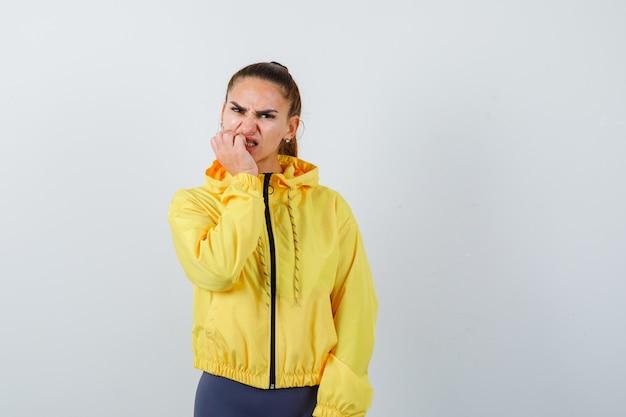 Portret młodej damy gryzie paznokcie w żółtej kurtce i wygląda na nerwowy widok z przodu
