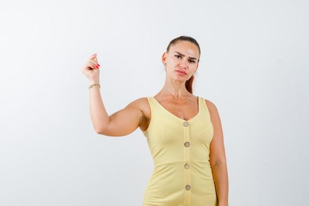 Portret młodej damy klikającej palcami podczas generowania pomysłu w żółtej sukience i wyglądającej elegancko z przodu