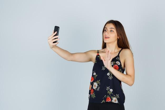 Portret młodej damy macha ręką na rozmowie wideo w bluzce i wygląda na zadowolony z widoku z przodu