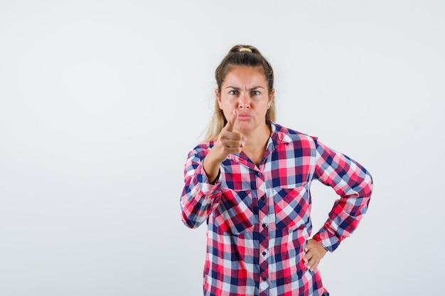 Portret młodej damy ostrzeżenie z palcem w kraciastej koszuli i patrząc nerwowy widok z przodu
