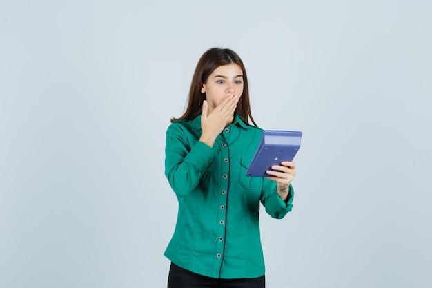 Portret młodej damy patrząc na kalkulator, trzymając dłoń na ustach w zielonej koszuli i patrząc zszokowany widok z przodu