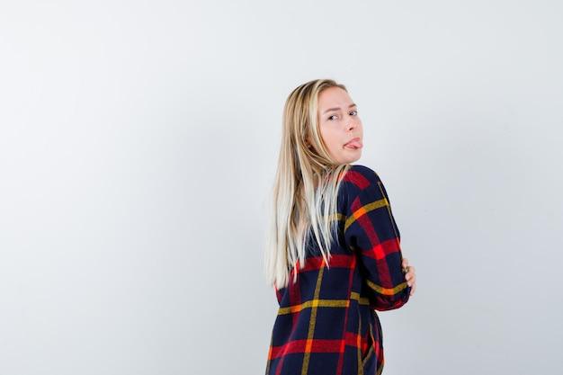 Portret młodej damy patrząc przez ramię, wystawiając język w kraciastej koszuli i patrząc pozytywnie z przodu