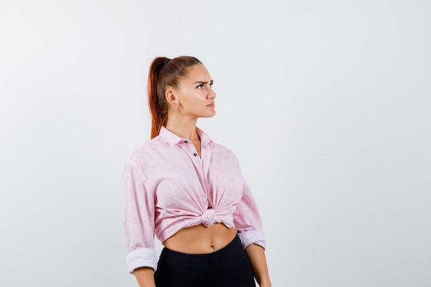 Portret młodej damy, patrząc w koszulę, spodnie i zamyślony widok z przodu