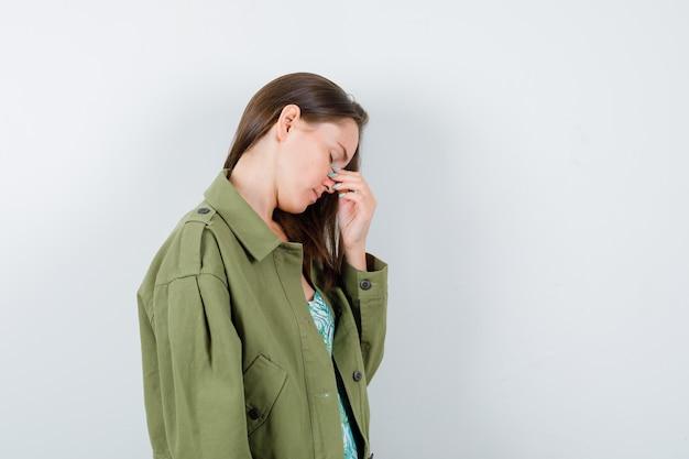 Portret młodej damy pocierającej nos i oczy w zielonej kurtce i patrzącej na zmęczony widok z przodu