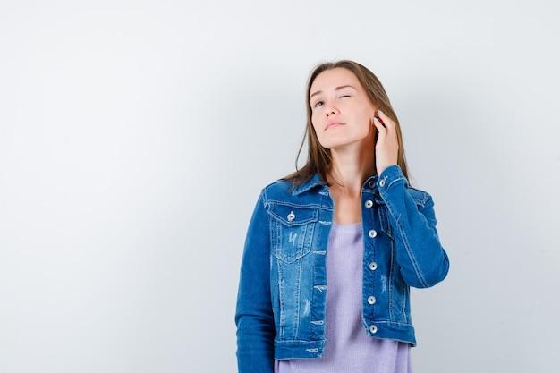 Portret młodej damy podsłuchującej prywatną rozmowę w koszulce, kurtce i patrzącej na ciekawy widok z przodu