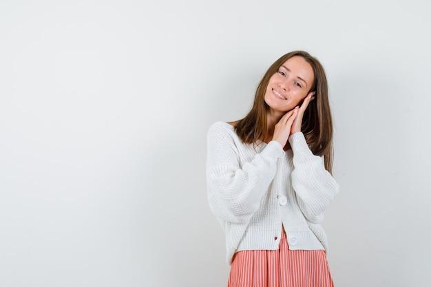 Portret młodej damy poduszkę twarzy na rękach w swetrze i spódnicy na białym tle