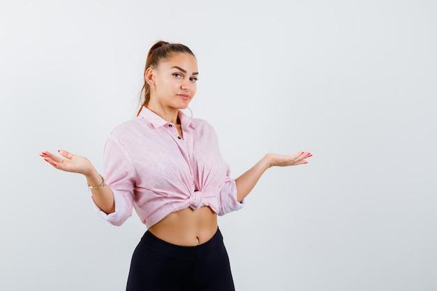 Portret młodej damy pokazując bezradny gest w koszuli, spodniach i patrząc niepewny widok z przodu
