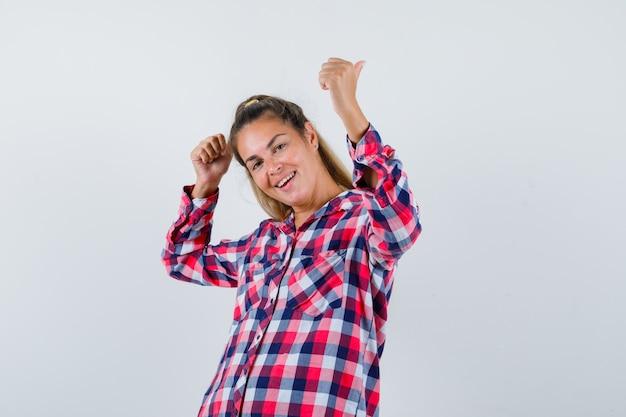 Portret młodej damy pokazując podwójne kciuki w kraciastej koszuli i patrząc szczęśliwy widok z przodu