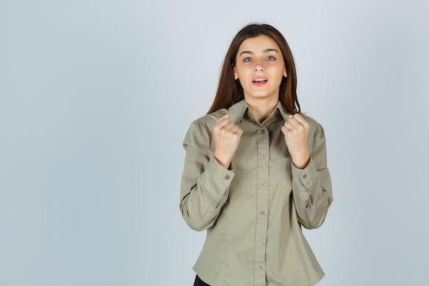 Portret młodej damy pokazujący gest zwycięzcy w koszuli i patrzący szczęśliwy widok z przodu