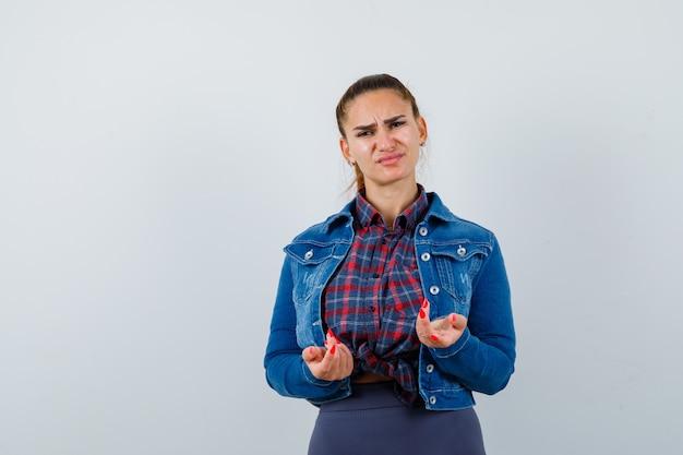 Portret młodej damy pokazujący nieświadomy gest w koszuli, kurtce i patrzący na rozczarowany widok z przodu