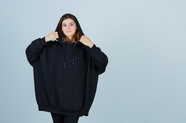 Portret młodej damy pozuje stojąc w obszernej bluzie z kapturem, spodniach i ładnym widokiem z przodu