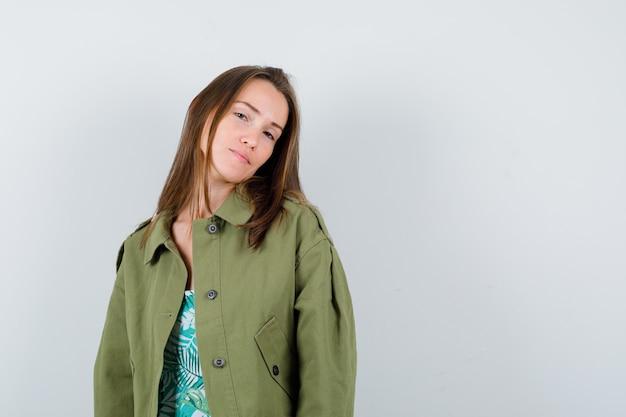 Portret młodej damy pozuje w zielonej kurtce i wygląda ładny widok z przodu