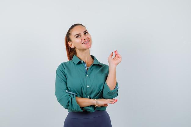 Portret młodej damy pozuje z podniesioną ręką, patrząc w górę w zielonej koszuli i patrząc marzycielski widok z przodu