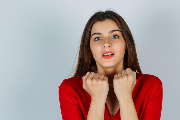 Portret młodej damy stojącej w przestraszonej pozie w czerwonej bluzce i przestraszonej