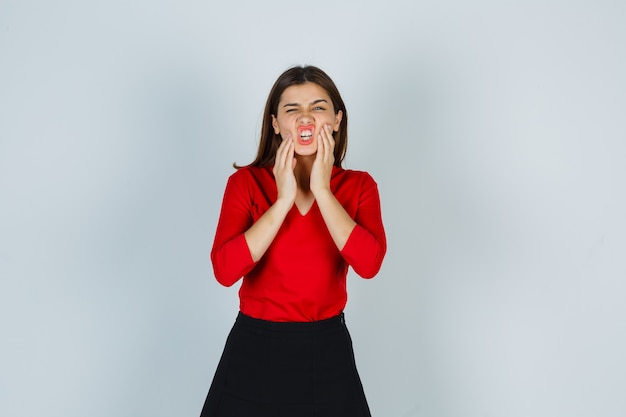Portret młodej damy, trzymając się za ręce na policzkach w czerwonej bluzce