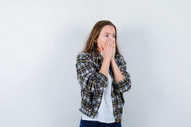 Portret młodej damy, trzymając się za ręce na ustach w t-shirt, kurtkę i patrząc przestraszony widok z przodu