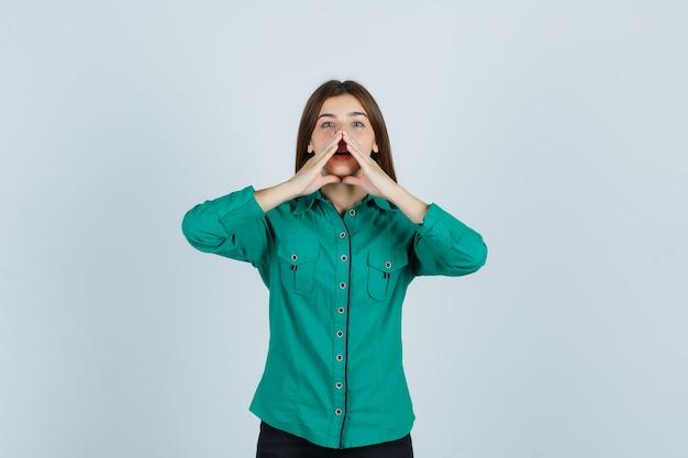 Portret młodej damy, trzymając się za ręce w pobliżu ust, mówiąc tajemnicę w zielonej koszuli i patrząc ciekawy widok z przodu