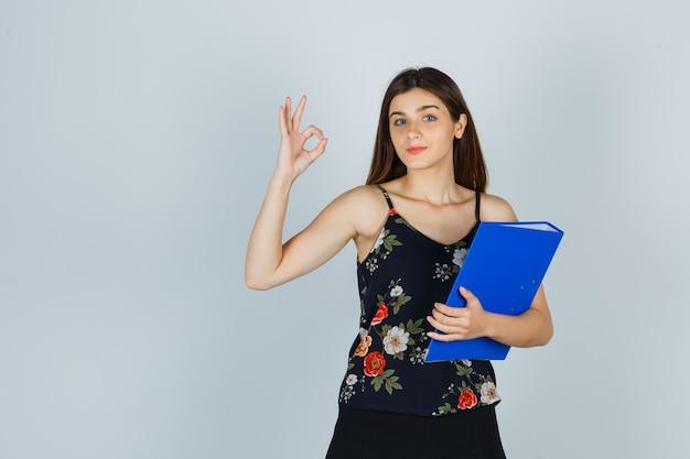 Portret młodej damy trzymającej folder, pokazując ok gest w bluzce, spódnicy i patrząc pewnie z przodu