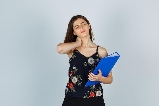 Portret młodej damy trzymającej folder, z bólem szyi w bluzce, spódnicy i wyglądającym na zmęczonego widoku z przodu