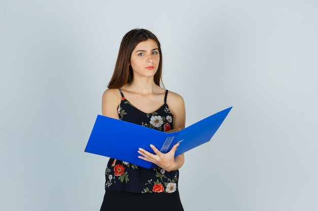 Portret młodej damy trzymającej otwarty folder w bluzce i patrzącej na zamyślony widok z przodu