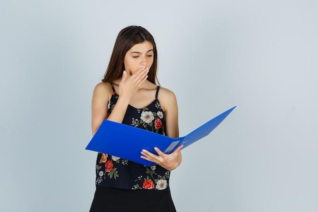 Portret młodej damy trzymającej rękę na ustach, patrząc na folder w bluzce i patrząc zdziwiony widok z przodu