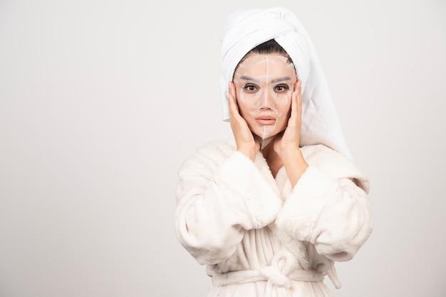 Portret młodej damy w szlafrok i ręcznik na głowie, dotykając jej twarzy maską