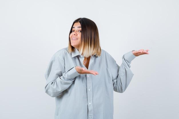 Portret młodej damy witającej coś w przewymiarowanej koszuli i wyglądającej na szczęśliwego widoku z przodu