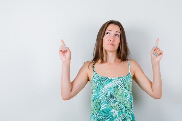 Portret młodej damy, wskazując w górę w bluzce i patrząc zamyślony widok z przodu