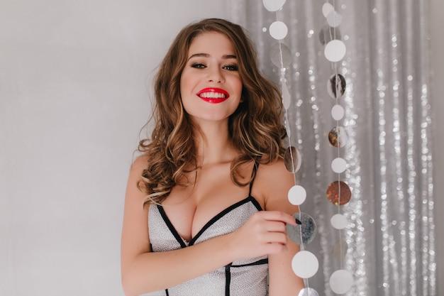 Portret młodej damy z czerwonymi ustami w błyszczącej górze uśmiechając się na białej ścianie z brokatem.