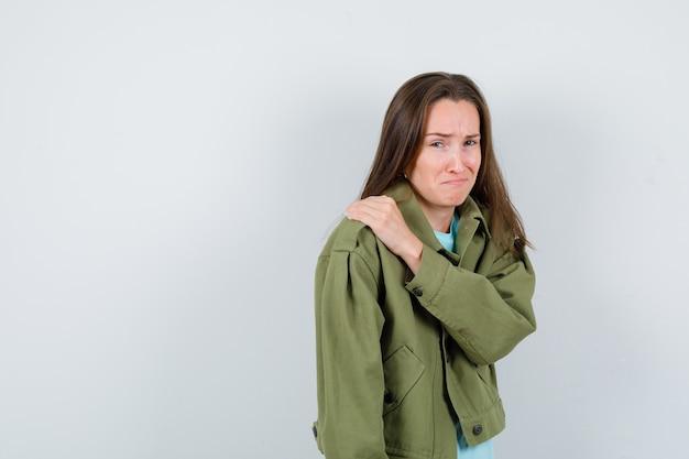 Portret młodej damy z ręką na ramieniu w koszulce, kurtce i patrząc obrażony widok z przodu