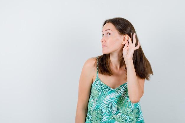 Portret młodej damy z ręką za uchem w bluzce i patrzący poważny widok z przodu