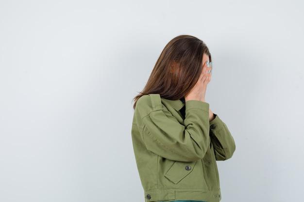 Portret młodej damy zakrywającej twarz rękami w koszulce, kurtce i patrzącym tęsknym widokiem z przodu