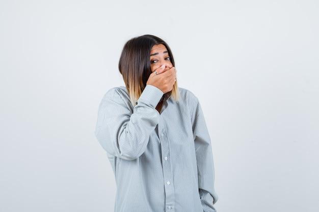 Portret młodej damy zakrywającej usta ręką w zbyt obszernej koszuli i patrzącej na przestraszony widok z przodu