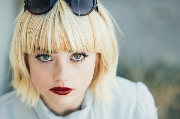 Portret młodej, delikatnej rudej nastolatka ze zdrową piegowatą skórą na sobie pasiasty top patrząc na kamerę z poważnym lub zamyślonym wyrazem. kaukaska modelka z rudymi włosami pozuje w pomieszczeniu
