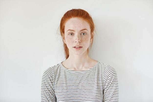 Portret młodej delikatnej rudowłosej nastolatki ze zdrową piegowatą skórą na sobie pasiasty top, patrząc z poważnym lub zamyślonym wyrazem twarzy. kaukaski modelka z rudymi włosami pozowanie w pomieszczeniu