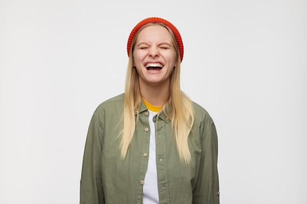 Portret młodej, dobrze wyglądającej blondynki marszczy brwi, śmiejąc się z zamkniętymi oczami, trzymając ręce w dół, pozując na niebiesko
