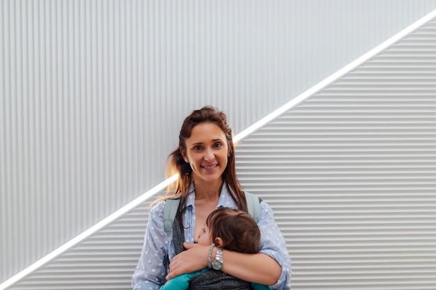 Portret młodej dorosłej matki niosącej roczne dziecko