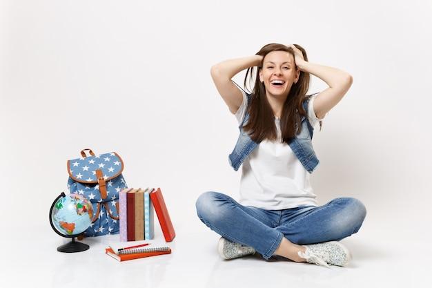 Portret młodej dorywczo radosnej roześmianej kobiety, która trzyma ręce na głowie, siedząc w pobliżu globu plecaka szkolne książki na białym tle