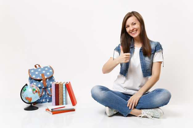 Portret młodej dorywczo uśmiechniętej kobiety studentki w dżinsowych ubraniach pokazującej kciuk do góry siedzący w pobliżu kuli ziemskiej, plecaka, podręczników szkolnych na białym tle