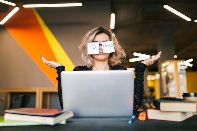 Portret młodej dość zmęczonej kobiety z papierowymi naklejkami na okularach siedzącej przy stole w czarnej koszuli pracującej na laptopie w biurze coworkingowym, zabawny wyraz twarzy, zdziwiona emocja, problem