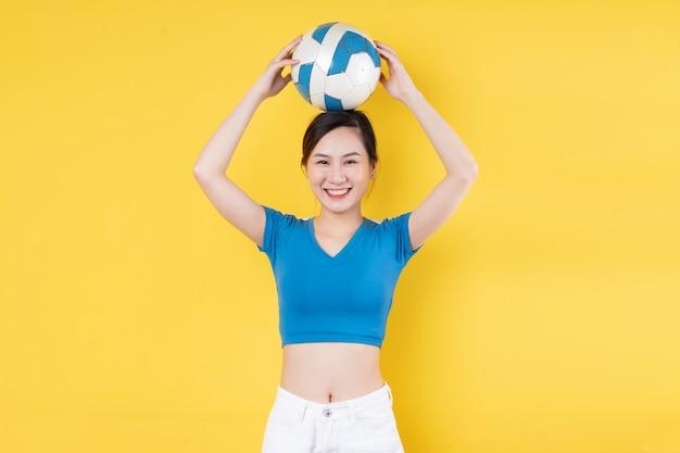 Portret młodej dynamicznej dziewczyny trzymającej piłkę w ręku na żółtym tle