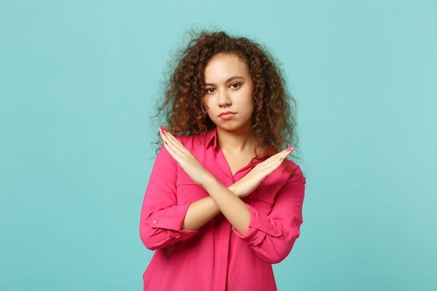 Portret młodej dziewczyny afryki w różowe ubrania dorywczo pokazując gest stop skrzyżowanymi rękami na białym tle na tle niebieskiej ściany turkus. koncepcja życia szczere emocje ludzi. makieta miejsca na kopię.