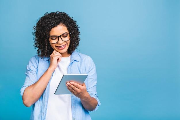 Portret młodej dziewczyny amerykańskiego studenta z kręconymi włosami afrykańskimi, trzymając cyfrowy tablet i uśmiechając się stojąc na na białym tle niebieskim tle z miejscem na tekst, logo lub reklamę.