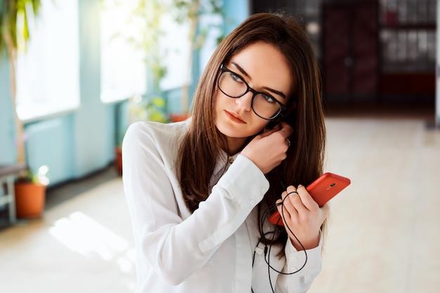 Portret młodej dziewczyny atrakcyjne na uniwersytecie, wkładając słuchawki do uszu
